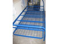Sturdy Blue metal twin beds, one is a truckle that slides underneath for storage