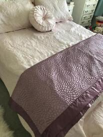 Pale pink double bed cover with two pillow shams and a dusky pink throw.