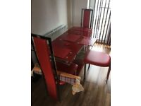 Glass table with chrome chairs upholstered in red faux leather