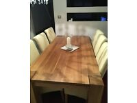 Solid oak modern dining table with six cream high back chairs