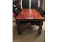 Mahogany wood dining table and brown chairs