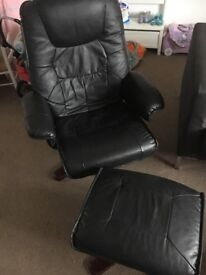 Reclinable Black faux leather arm chair with stool.