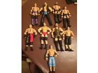 collection of wwe wrestling figures including belts and ring