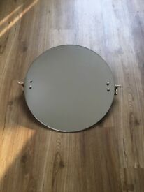 Round bathroom mirror with brass wall fittings. N