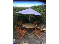 Wooden table and chairs with parasol and covers