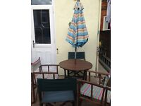 Wooden round garden table, 4 directors chairs and parasol.