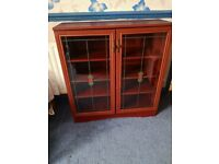 A MAHOGANY EFFECT GLAZED DOOR BOOK CASE