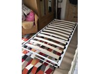 Single Trundle Bed. White, metal frame with wooden slats.