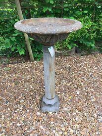 Large cast iron bird bath on a pedestal.