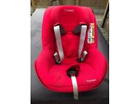 A maxi cosi 2 way pearl car seat with isofix base in red