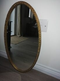 Oval, gold wall mirror