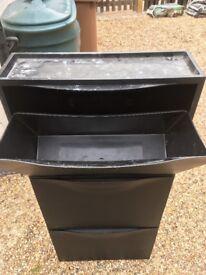Black plastic three tier shoe storage system from ikea.