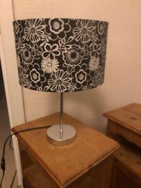 Black and white flower lampshade on a simple modern silver lamp-stand