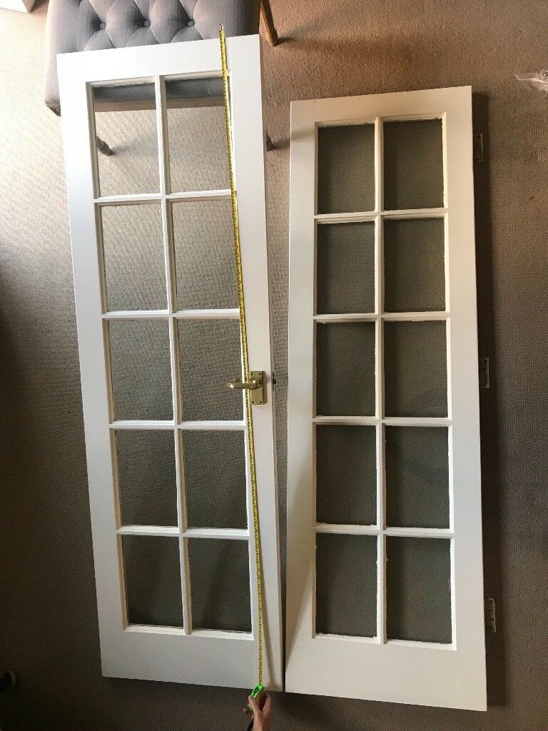Two White Solid Wood Internal Doors With Glass Panels And Brass Colored Handles