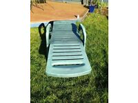 Green plastic sun lounger and cushion