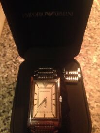 Genuine emporio armani watch next to new classic men's watch
