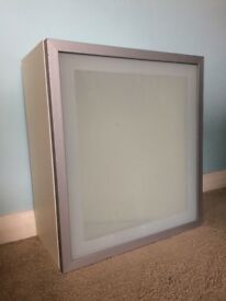 White bathroom wall cabinet with silver and glass door