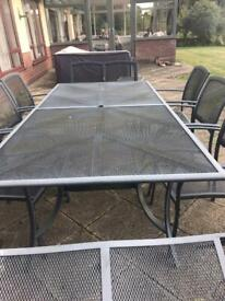Outdoor dining table and chairs set with cushions and two small tables.