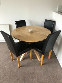 Round oak dining table and four chairs