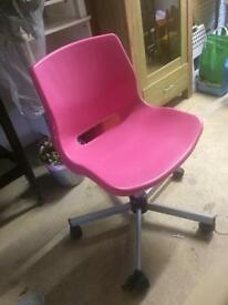 Pink office plastic chair on wheels