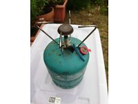 small refillable gas bottle about 3/4 full with burner