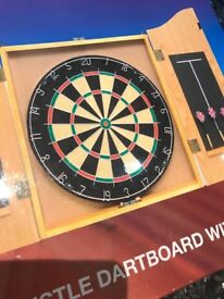 Unused dartboard with wooden cabinet