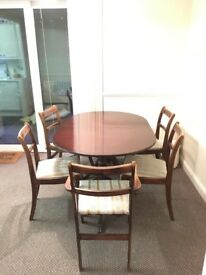 Mahogany extendable dining table with clawed feet and five chairs