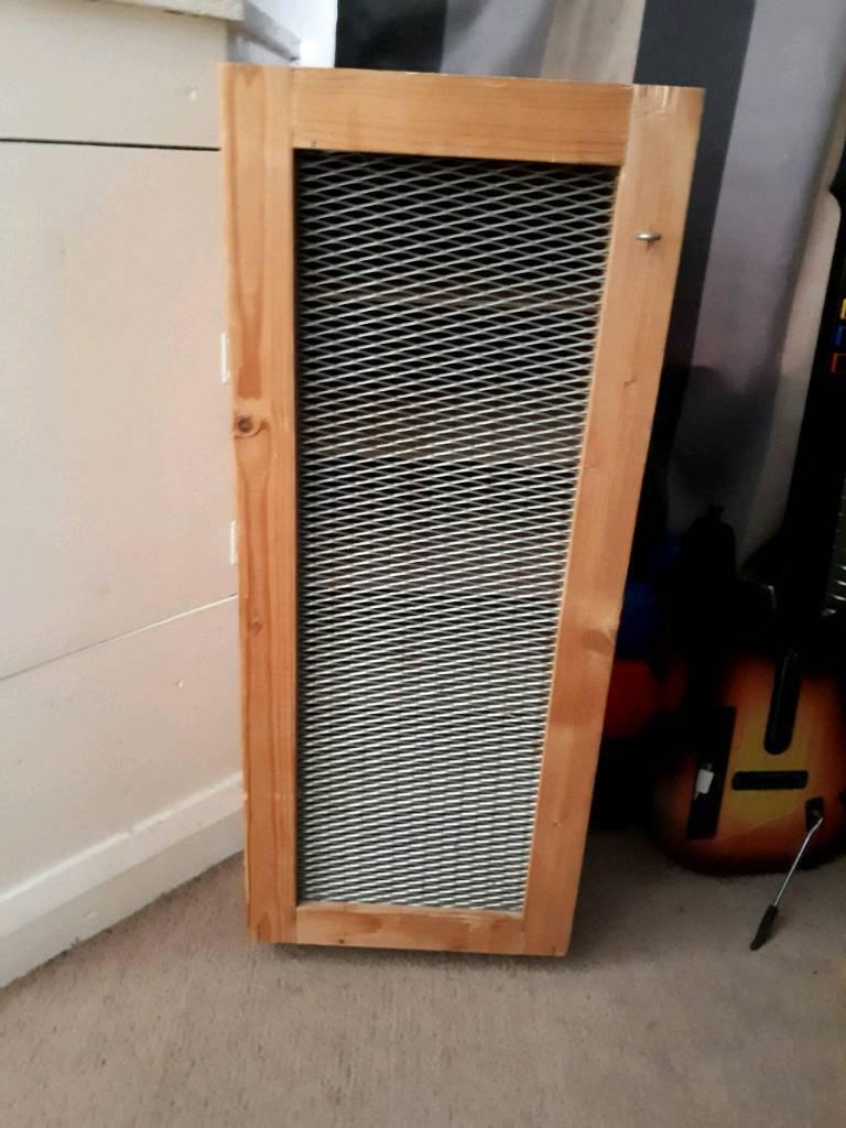 Wooden shelving cupboard unit with metal mesh door & wheels. Good condition.