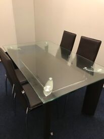 Glass dining room table with 4 leather chairs. Brand new ( 5 months old ) mint condition was £899
