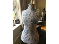 White and blue mannequin on white wooden stand