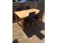 Oak dining table and 4 brown faux leather chairs.