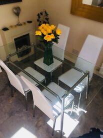 Glass table and 5 white chairs (only 4 in photo)