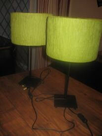 Two green lamp shades on slim black stands
