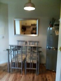 Dining table with glass top and four chairs