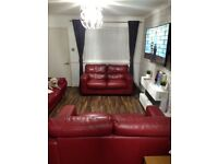 Two red leather two seater sofas in immaculate condition.