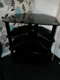 Black glass unit, table lamp, cushions and rug