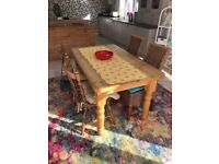 Solid chestnut dining table and four chairs. Table les come off for transport.