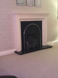 Black fire with granite hearth and mantle and white plaster surround