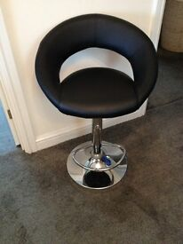 Black leather and chrome kitchen bar stool with adjustable height and foot rest