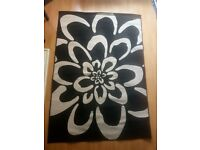 Large black and cream floral rug. Good condition.