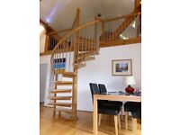 Beautiful wooden spiral staircase with silver metal spindles