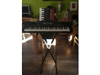 Electric organ with adjustable stand and book with songs