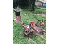Old vintage lawn mower and rotavator