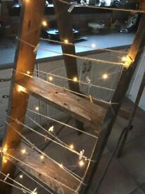 Rustic ladders with fairy lights and pegs