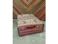 large ottoman coffee table upholstered in handmade vintage Moroccan Berber kilim and vintage leather