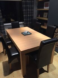 Extendable Oak dining set with 8 leatherette chairs.