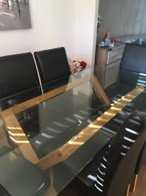 Glass dining table with 6 brown leather chairs, some tiny scratches with kids moving base