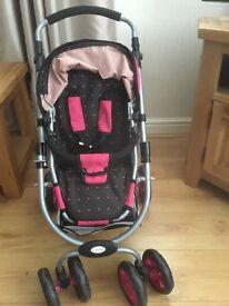 Dolls stroller 2 handle heights,has a basket underneath,black & pink.