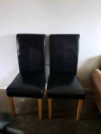 2 faux leather chairs in black.