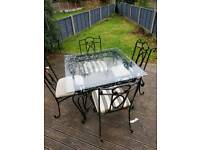 Glass top metal table with 4 chairs